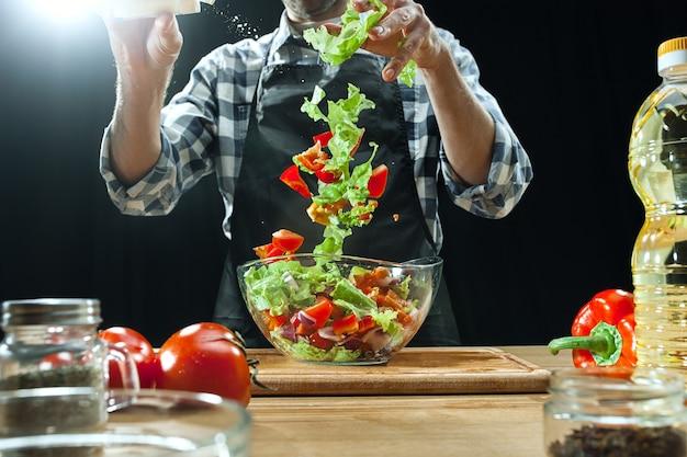 Przygotowywanie sałatki. kobieta szef kuchni cięcia świeżych warzyw. proces gotowania. selektywna ostrość. zdrowa żywność, kuchnia, sałatka, dieta, koncepcja ekologicznej kuchni