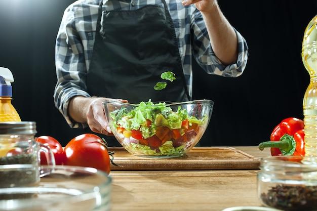 Przygotowywanie sałatki. kobieta szef kuchni cięcia świeżych warzyw. proces gotowania. selektywna ostrość