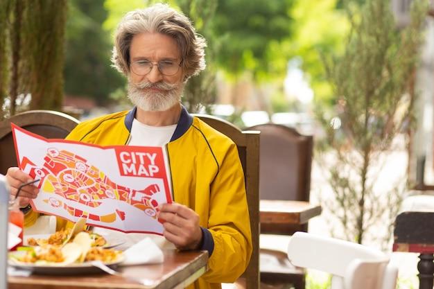 Przygotowywanie się. skoncentrowany mężczyzna siedzący w ulicznej kawiarni z mapą miasta w dłoniach przygotowujący się do spaceru.