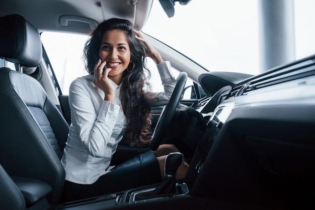 Przyjaciel dzwoni. piękna kobieta próbuje swojego nowego samochodu w salonie samochodowym