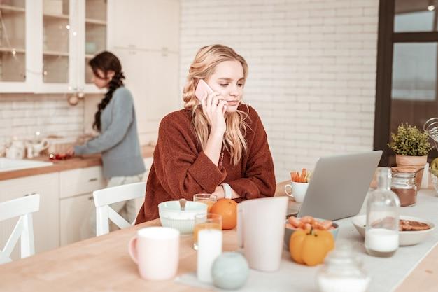 Przyjaciel gotuje za. zajęta, zdecydowana blondynka w pomarańczowym swetrze oversize po telefonie w porze śniadania