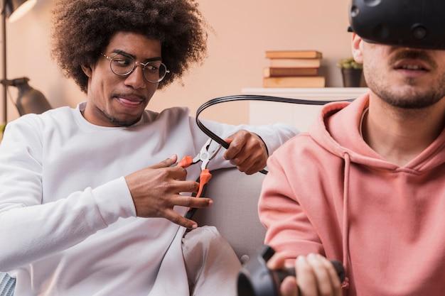 Przyjaciel gra dowcip na znajomego z wirtualnym zestawem słuchawkowym