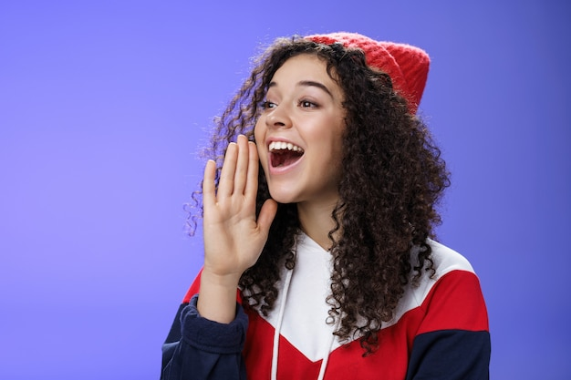Przyjaciel krzyczy przez ulicę, aby zwrócić uwagę. portret beztroskiej szczęśliwej słodkiej kobiety w czapce i bluzie trzymającej dłoń w pobliżu otwartych ust, patrząc z uśmiechem w lewo, jak dzwoniący kolega z głośnym krzykiem.