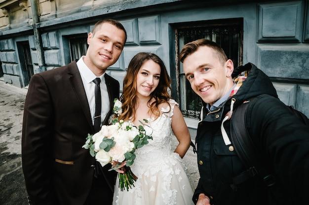 Przyjaciel nowożeńcy robi selfie z panną młodą nad ulicą starego miasta.