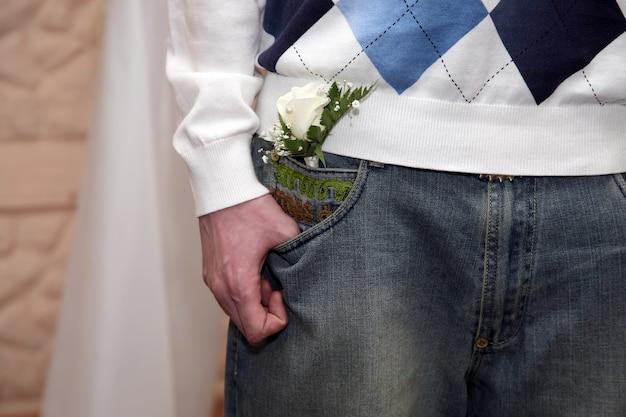 Przyjaciel pana młodego z weselnym kwiatkiem w kieszeni spodni