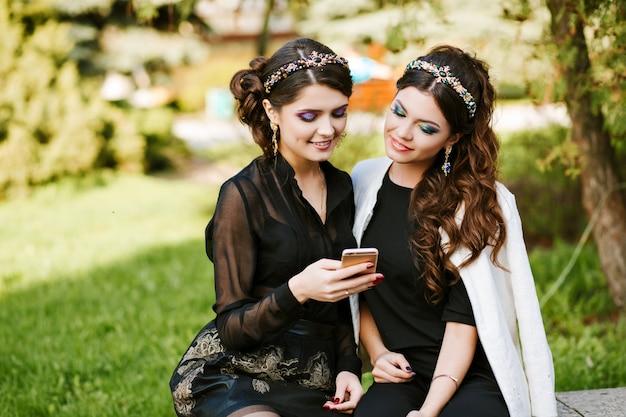 Przyjaciel patrzy na telefon i omawia coś. młoda stylowa kobieta na imprezie z jasnym wieczorowym makijażem i modną biżuterią.
