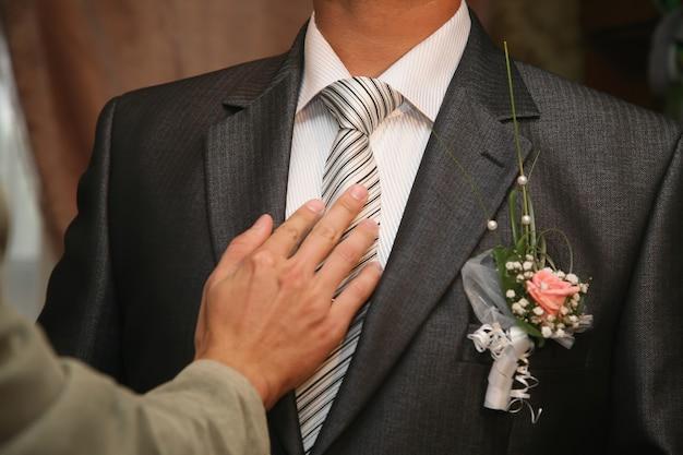 Przyjaciel prostuje krawat pana młodego