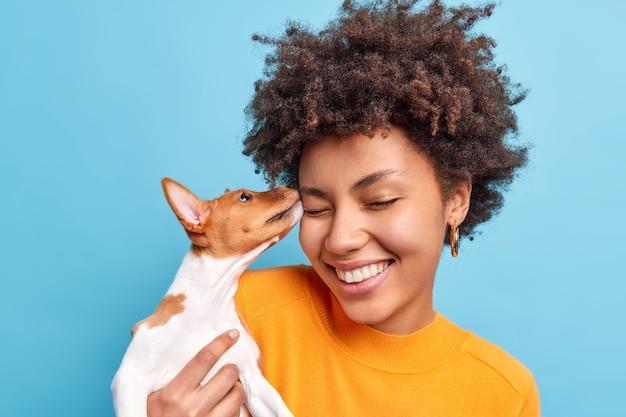 Przyjaciel rodziny. bliska strzał szczęśliwy kręcone włosy kobiety bawi się z psem wyraża pozytywne emocje lubi zwierzęta. mały rodowodowy szczeniak liże twarz właściciela. adoptowany zwierzak. czuły szczere uczucia
