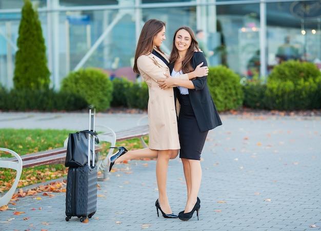 Przyjaciel wita z powrotem obejmując lotnisko. hala międzynarodowa brakujący uścisk i powitanie po przyjeździe
