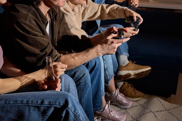 Przyjaciele bawią się grając w konsolę w domu, w pomieszczeniu, wieczorem lub w nocy. przyjaźń, wypoczynek, odpoczynek, koncepcja strony domowej. przycięte osoby z joystickami