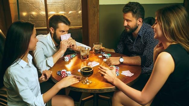 Przyjaciele bawią się podczas gry planszowej.