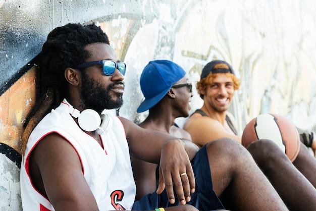 Przyjaciele bawią się podczas odpoczynku po meczu koszykówki ulicznej.