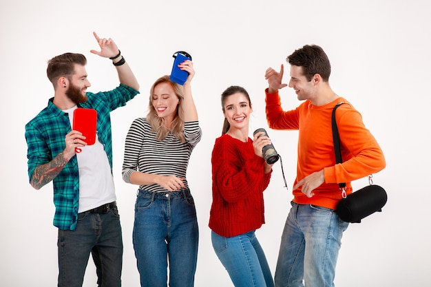 Przyjaciele bawią się razem uśmiechając się słuchając muzyki na głośnikach bezprzewodowych, tańcząc śmiejąc się na białym tle