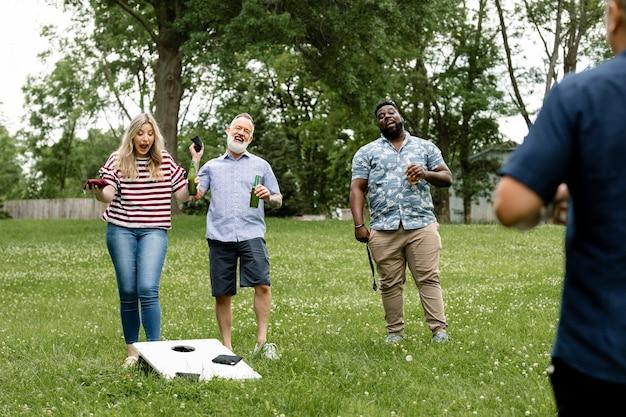 Przyjaciele bawią się w cornhole na letniej imprezie w parku