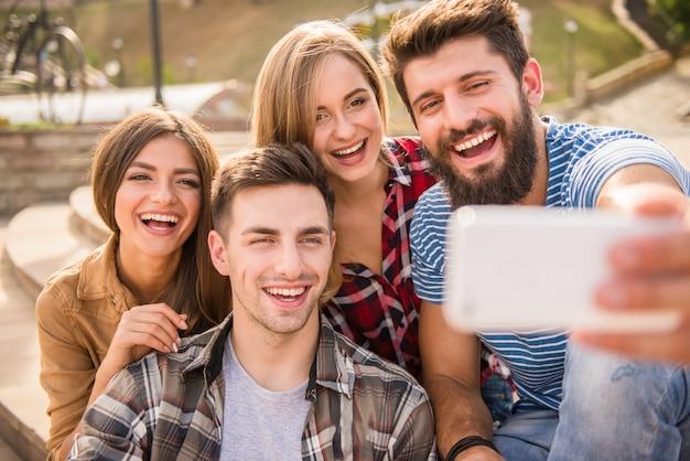 Przyjaciele biorą selfie przez telefon na ulicy.