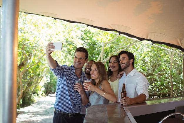 Przyjaciele biorąc selfie mając alkohol przy kasie
