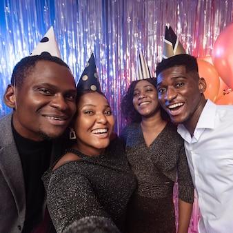 Przyjaciele biorący selfie na imprezie