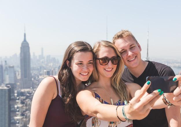 Przyjaciele biorący selfie z nowym jorkiem