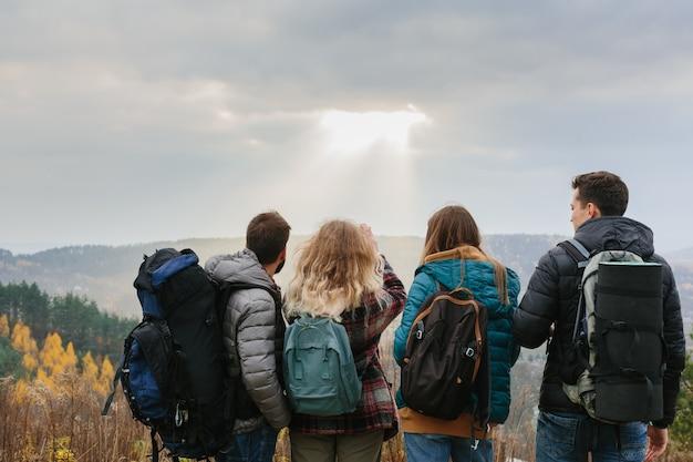 Przyjaciele cieszą się promieniami słońca wpadającymi przez chmury w górach