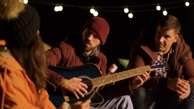 Przyjaciele cieszący się solówką na gitarze od jednego ze swoich przyjaciół na kempingu. zimna jesienna noc. retro samochód kempingowy.