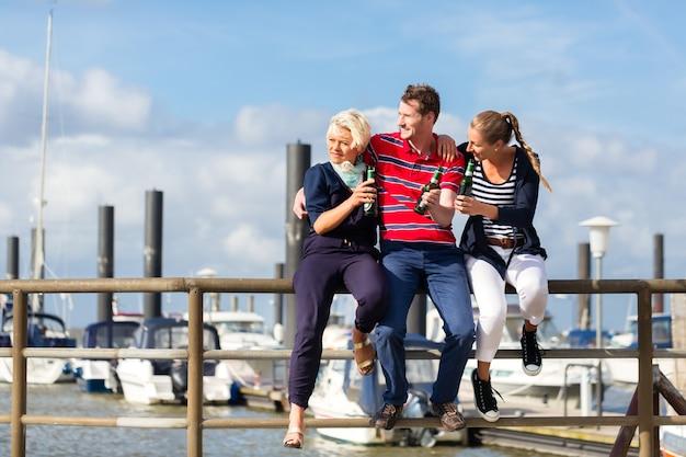 Przyjaciele cieszący się wakacjami na niemieckim molo statku nad morzem północnym pijąc piwo