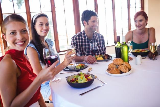 Przyjaciele cieszy się jedzenie i wino przy stołem w restauraci
