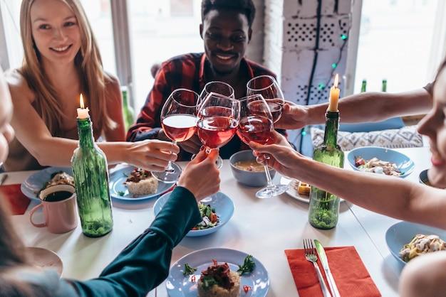 Przyjaciele co toast wokół stołu na kolacji.