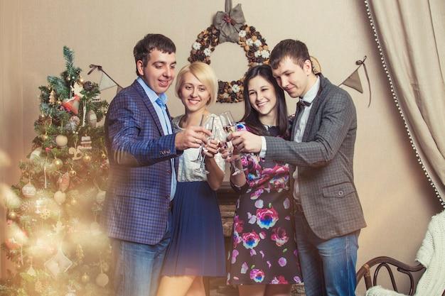 Przyjaciele czterech mężczyzn i kobiet z bacale świętują szampanem w świątecznym wnętrzu