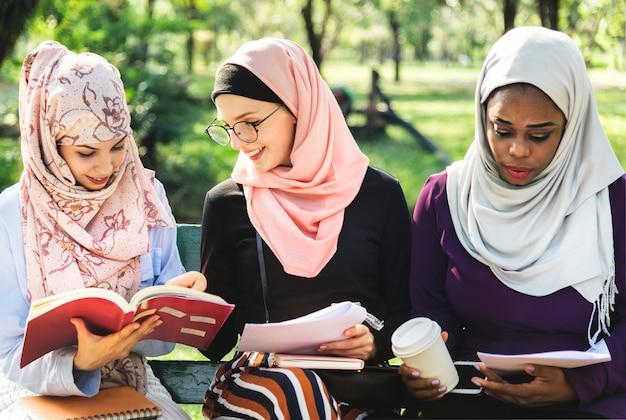 Przyjaciele czyta książkę wpólnie przy parkiem