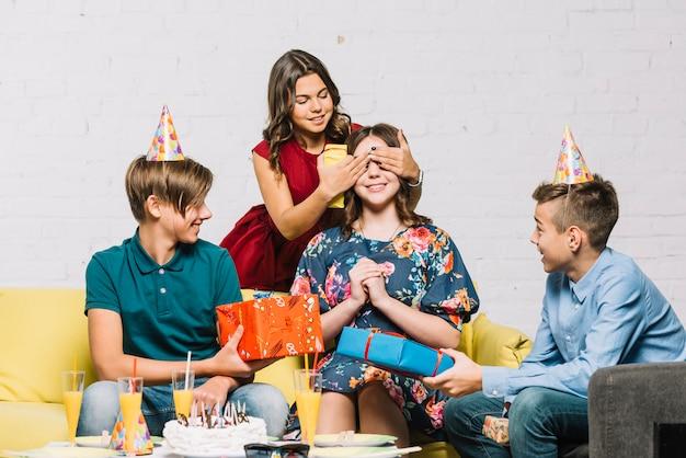 Przyjaciele dając prezenty do urodzinowej dziewczyny, zakrywając jej oczy na imprezie