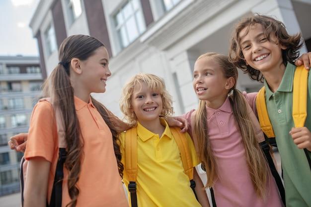 Przyjaciele. dzieci w wieku szkolnym bawiące się na boisku szkolnym i wyglądające na szczęśliwych