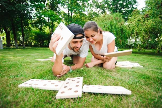 Przyjaciele graczy domina na zielonej trawie.