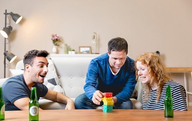 Przyjaciele grają w gry i piją piwo w domu