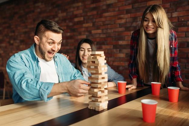 Przyjaciele grają w gry stołowe, skupiając się na wieży