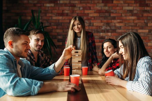 Przyjaciele grają w jengę, selektywnie koncentrując się na wieży