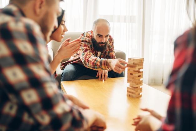 Przyjaciele grają w jengę w domu, mężczyzna wyciąga drewniany klocek z wieży.