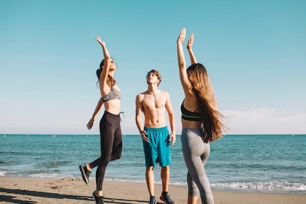 Przyjaciele grają w siatkówkę na plaży
