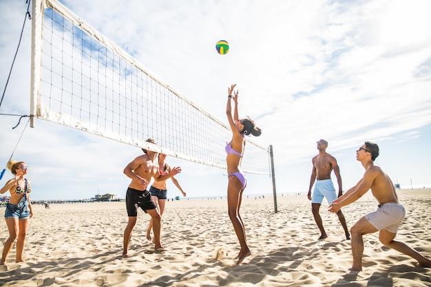 Przyjaciele grają w siatkówkę plażową