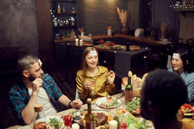 Przyjaciele grają w zgadywanie podczas kolacji