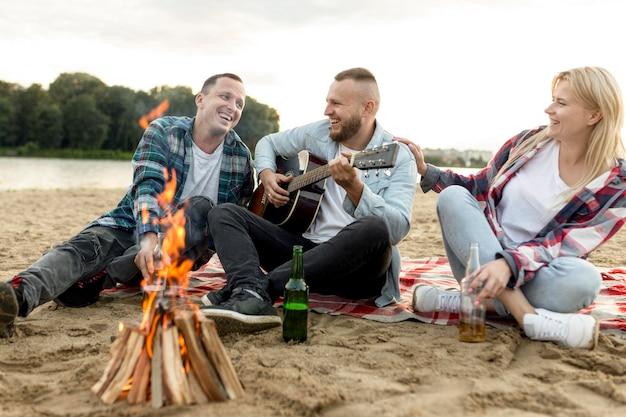 Przyjaciele grający na gitarze i śpiewający na plaży