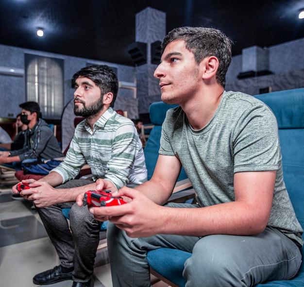 Przyjaciele grający w gry wideo online w klubie gier