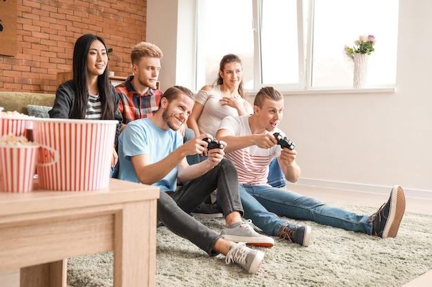 Przyjaciele grający w gry wideo w domu