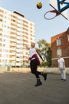 Przyjaciele grający w koszykówkę w pełnym ujęciu