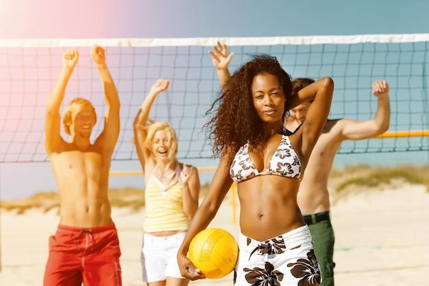 Przyjaciele grający w siatkówkę plażową