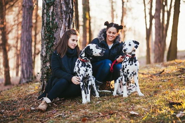 Przyjaciele i psy dalmatyńskie w parku.