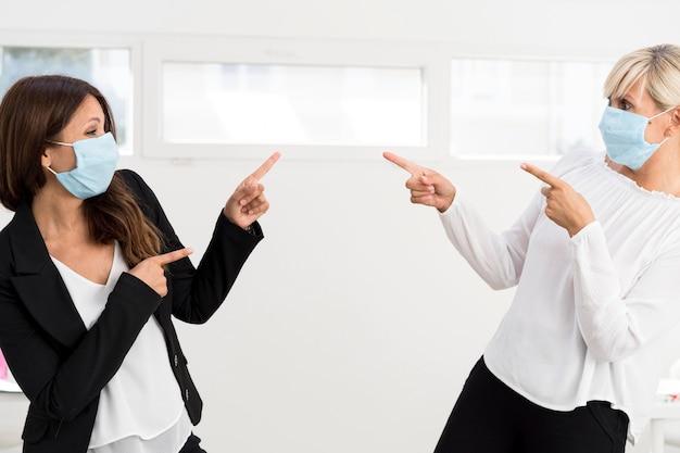 Przyjaciele i współpracownicy noszący maski ochronne w pracy