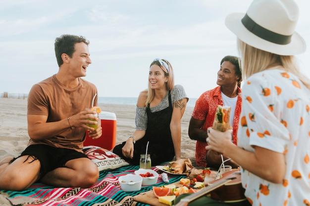 Przyjaciele jedzą jedzenie na pikniku na plaży