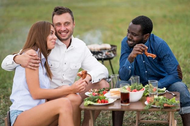 Przyjaciele jedzą obok grilla na świeżym powietrzu