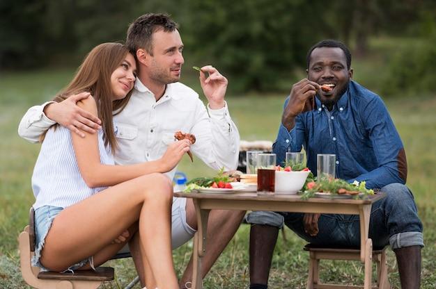 Przyjaciele jedzą obok grilla