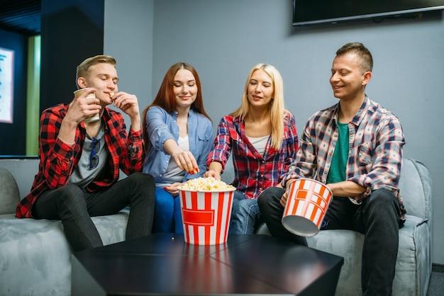 Przyjaciele jedzą popcorn i bawią się w sali kinowej przed seansem. młodzieży płci męskiej i żeńskiej siedzi na kanapie w kinie